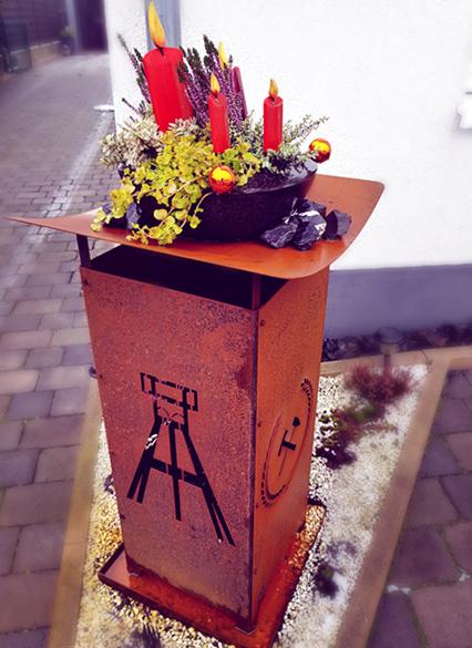 Dekorierte Feuersäule mit Ruhrgebiets-Motiv und Blumendekoration
